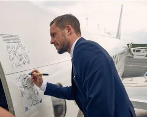 Islandsk fodboldspiller skriver sin autograf på Icelandairs Boeing 757-fly før afrejsen til Frankrig. (Foto: Icelandair)